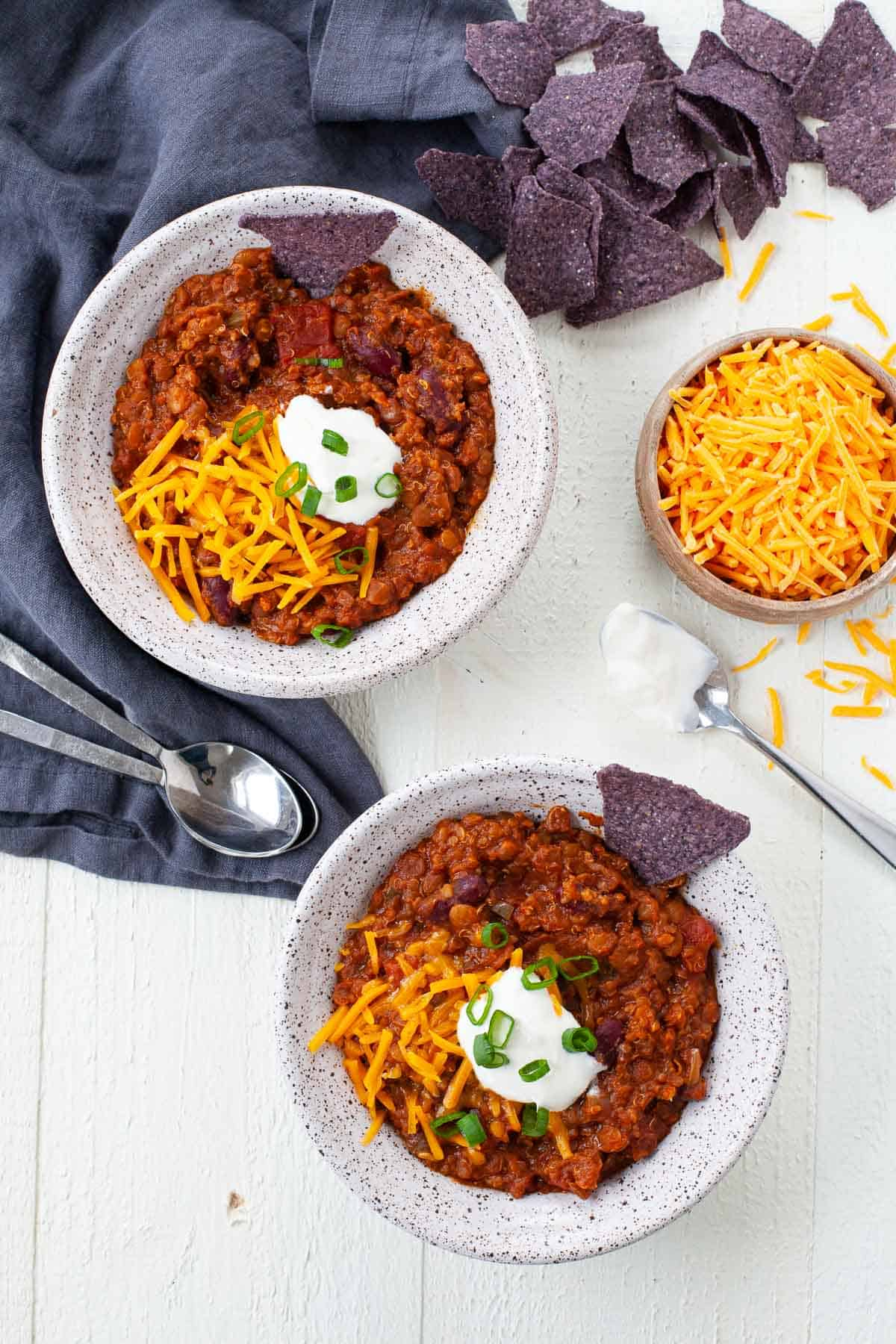 two bowls of vegetarian chili with tortilla chips, cheese, sour cream, scallions and bowl of cheese