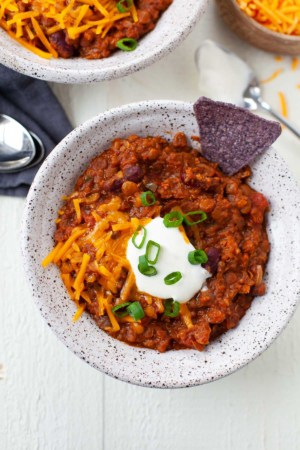 vegetarian chili with beans, quinoa, lentils, cocoa powder, tortilla chips, cheese, sour cream, and scallions