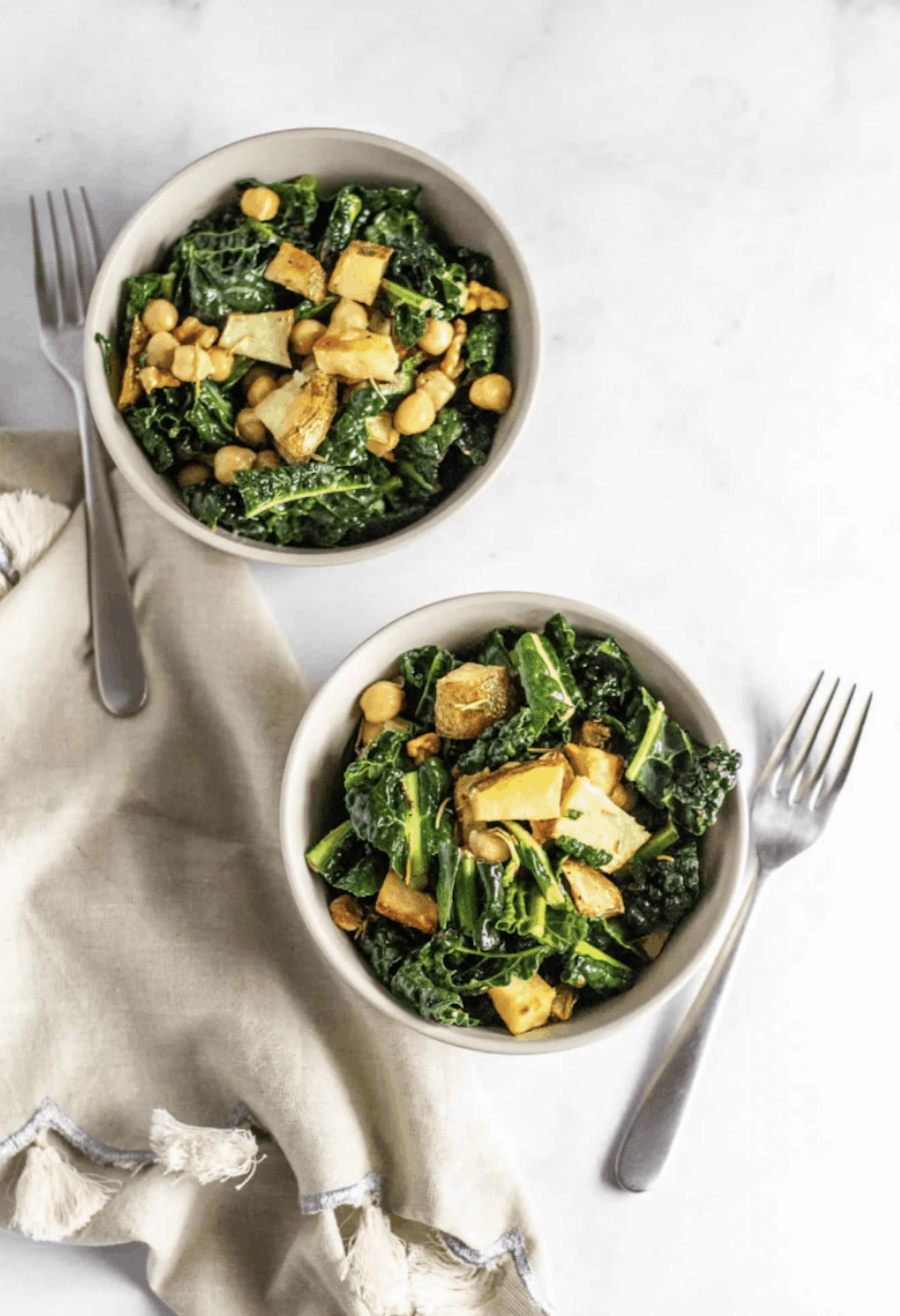 Two bowls of kale salad with crispy tofu and chickpeas on white background, two forks, and a beige linen napkin