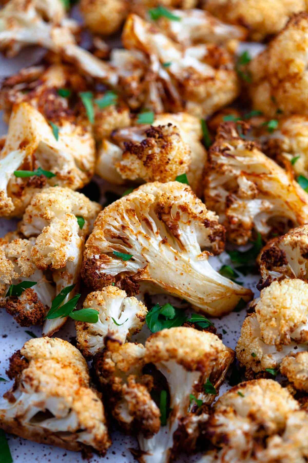 close up crispy crunchy golden brown air fryer cauliflower with parsley garnish