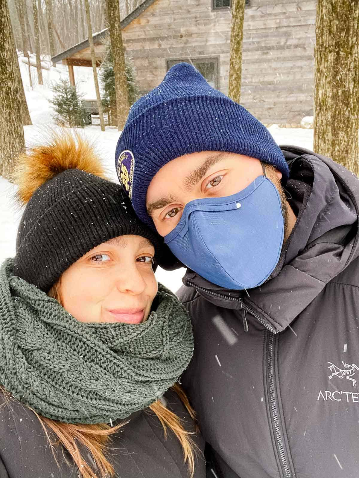 couple outside wearing winter hats in front of lodge at june farms