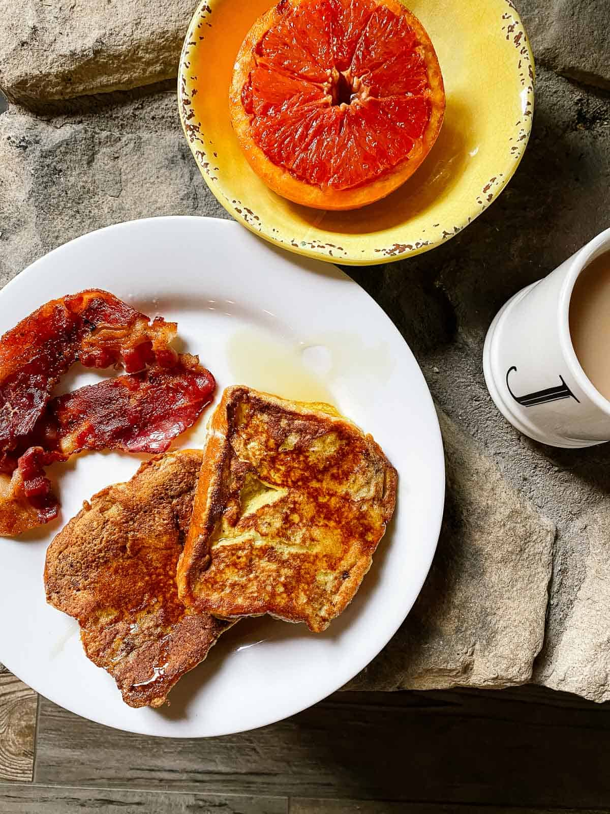 plate of french toast with syrup and bacon and bowl with grapefruit and mug of tea