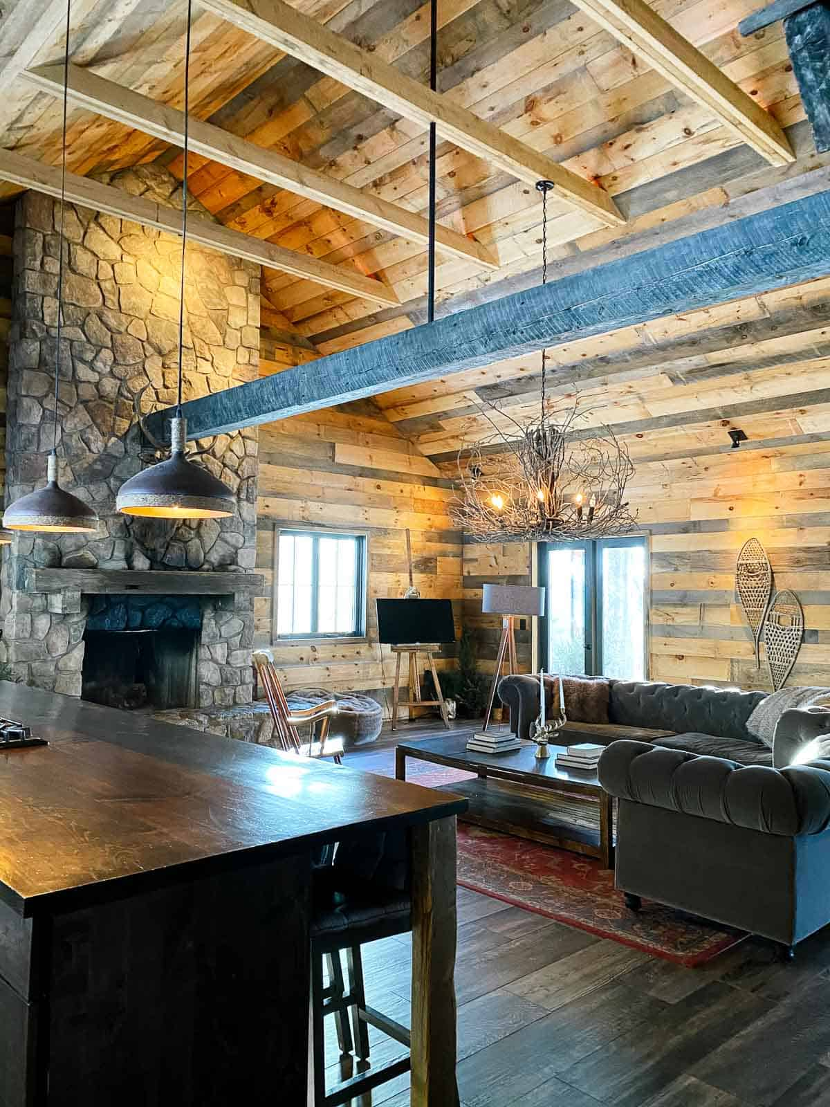 the lodge at june farms with wood beams and two grey couches and stone fireplace