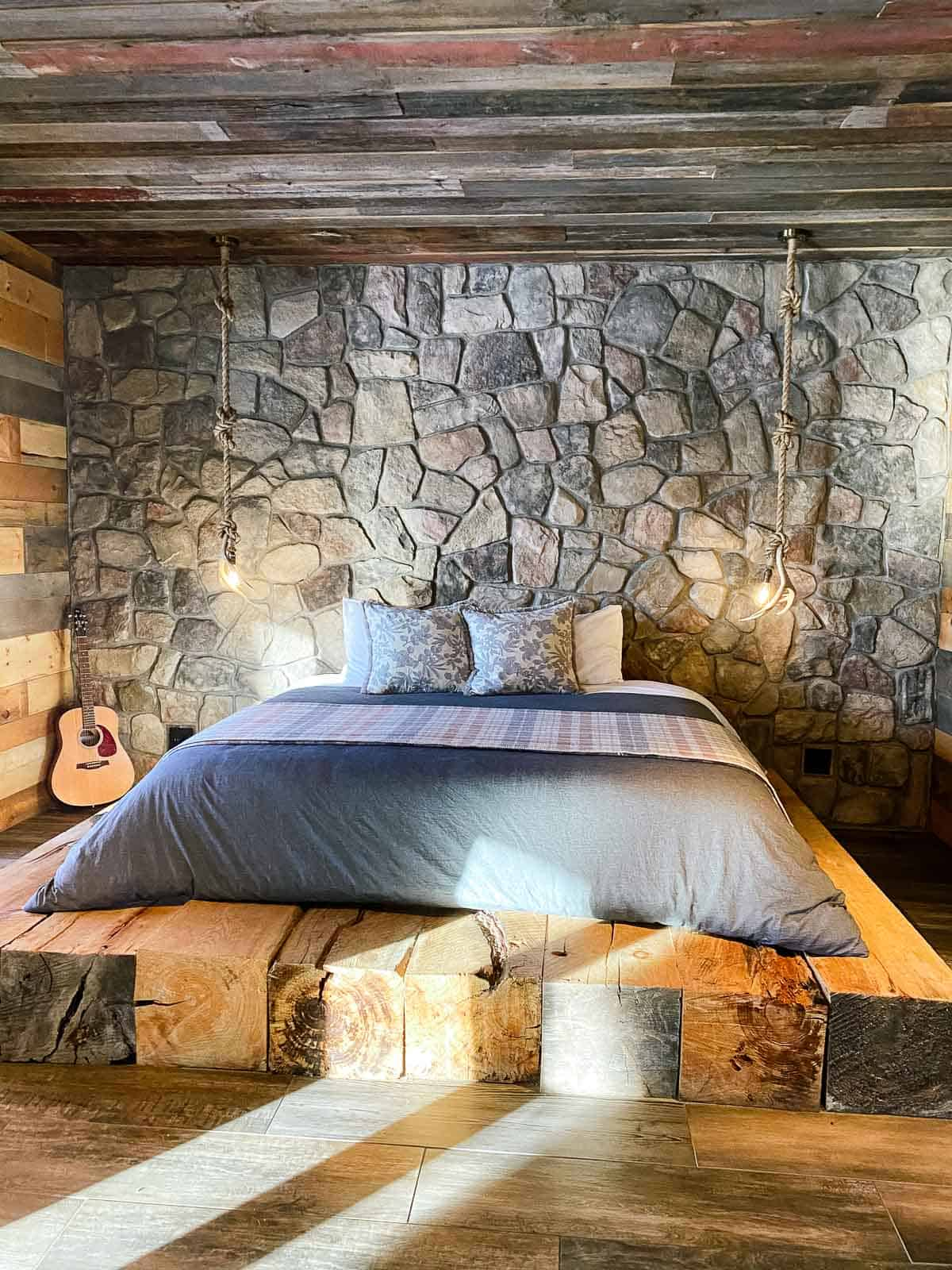 rustic bed with grey blanket in cabin on wood platform with stone wall behind it
