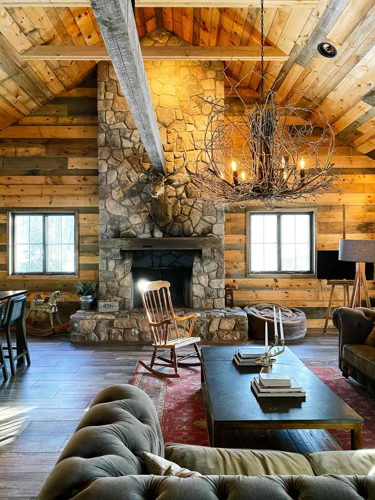 wood luxury cabin with stone fireplace and wood rocking chair and branch chandelier