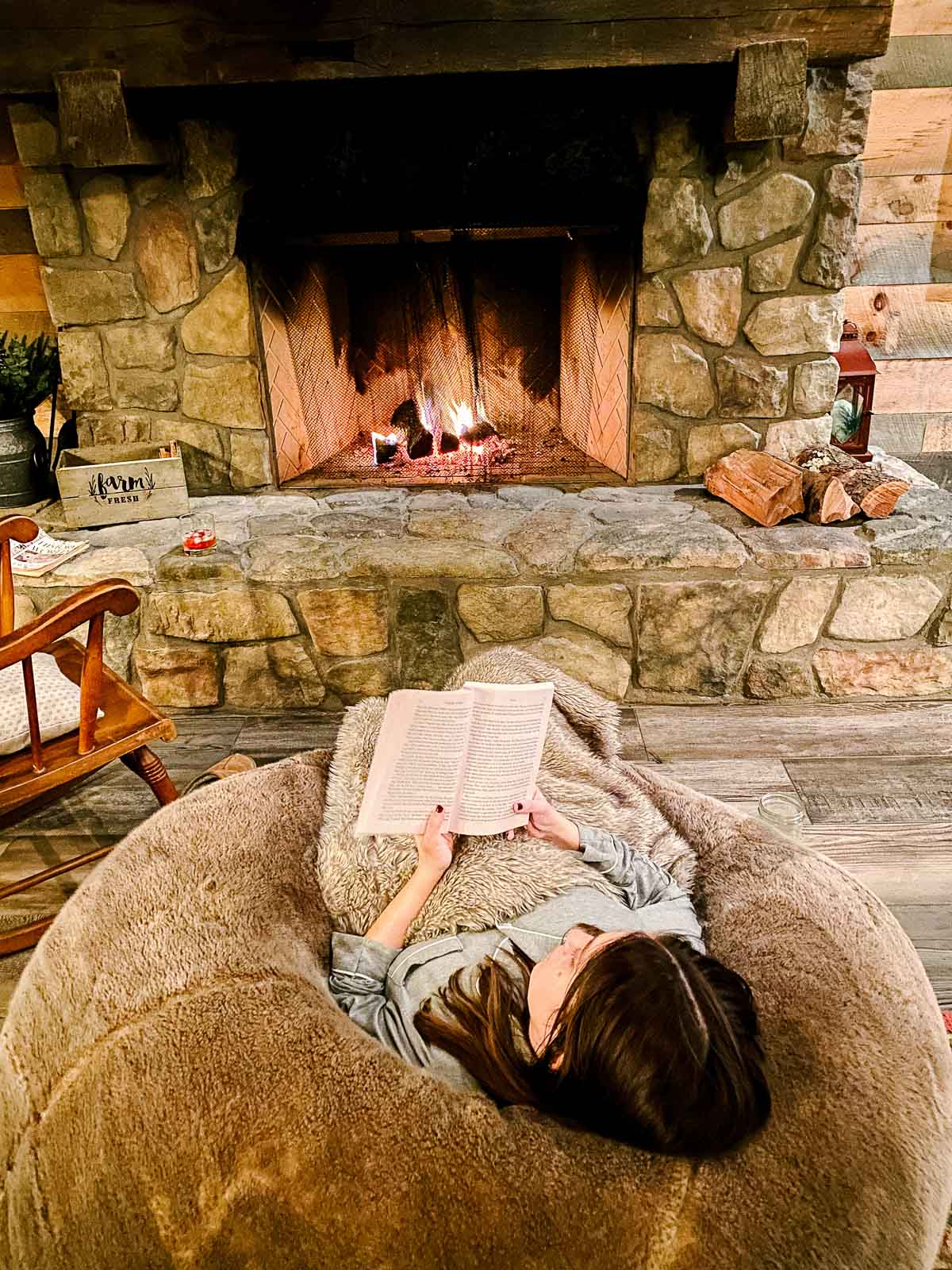 woman in pajamas on bean bag chair with fuzzy blanket in front of fire at cabin