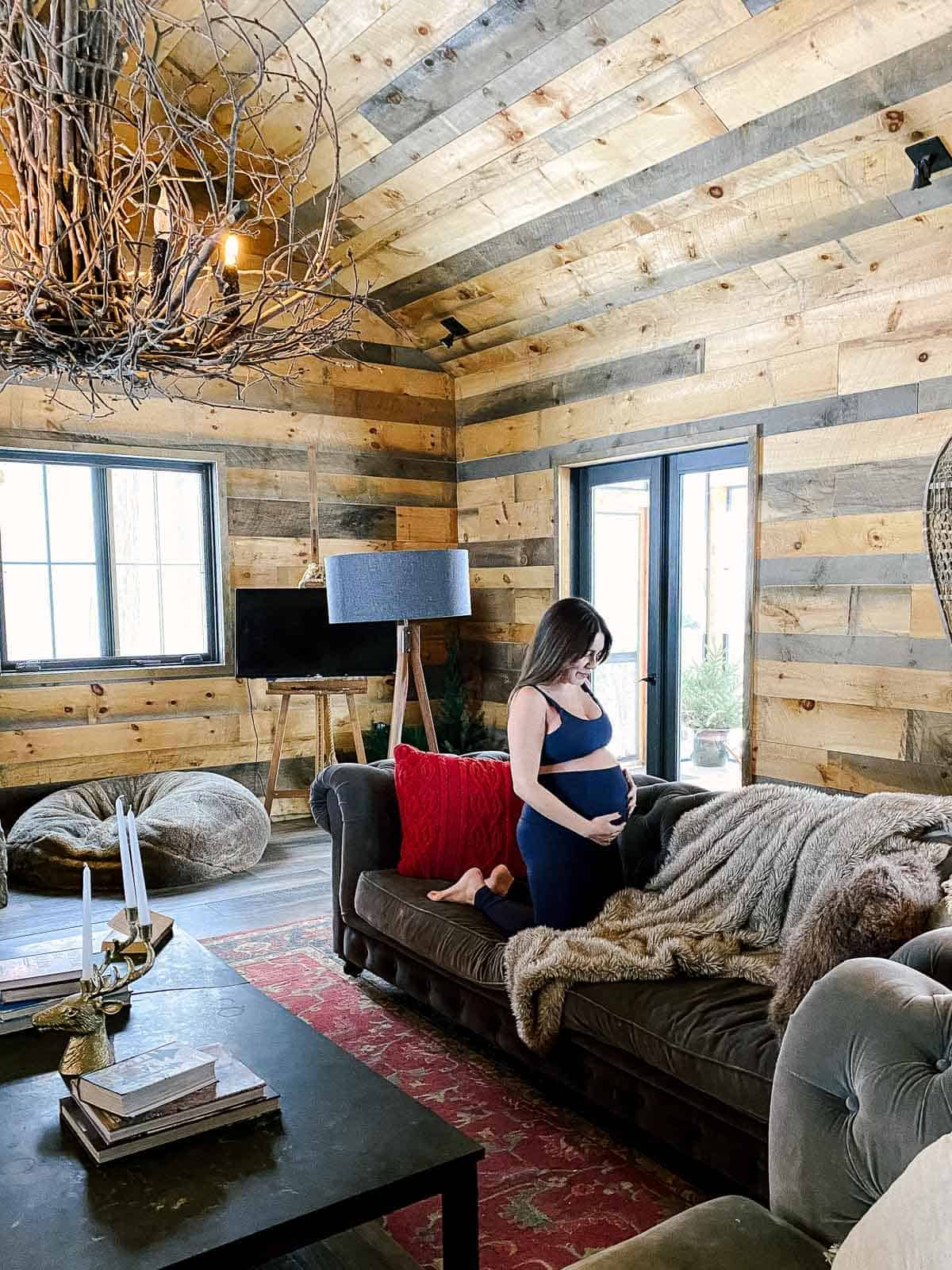 pregnant woman in yoga clothes on couch in cabin with wood walls and rustic chandelier