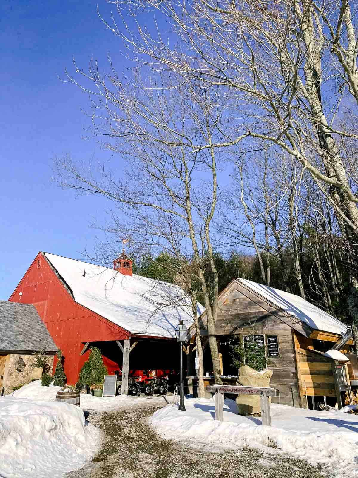 red barn with wood snack bar and blue sky with snow on the ground at june farms