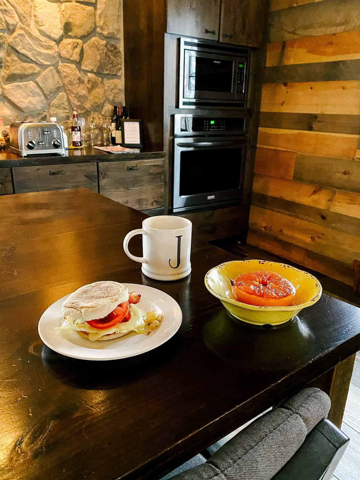 egg cheese tomato bacon breakfast sandwich and bowl with grapefruit and mug on table