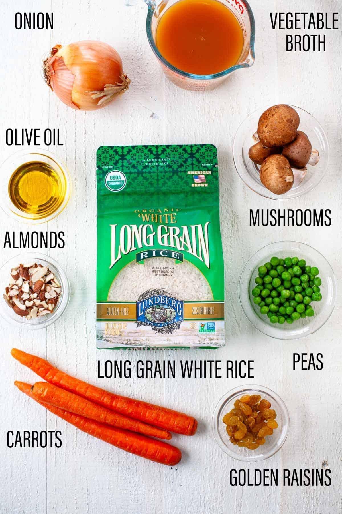 vegetarian rice pilaf ingredients on white background long grain white rice, sliced almonds, golden raisins