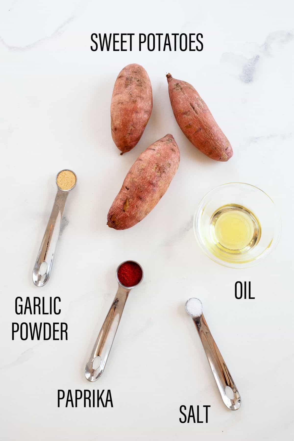 ingredients for air fryer sweet potato fries on white background garlic powder paprika three sweet potatoes