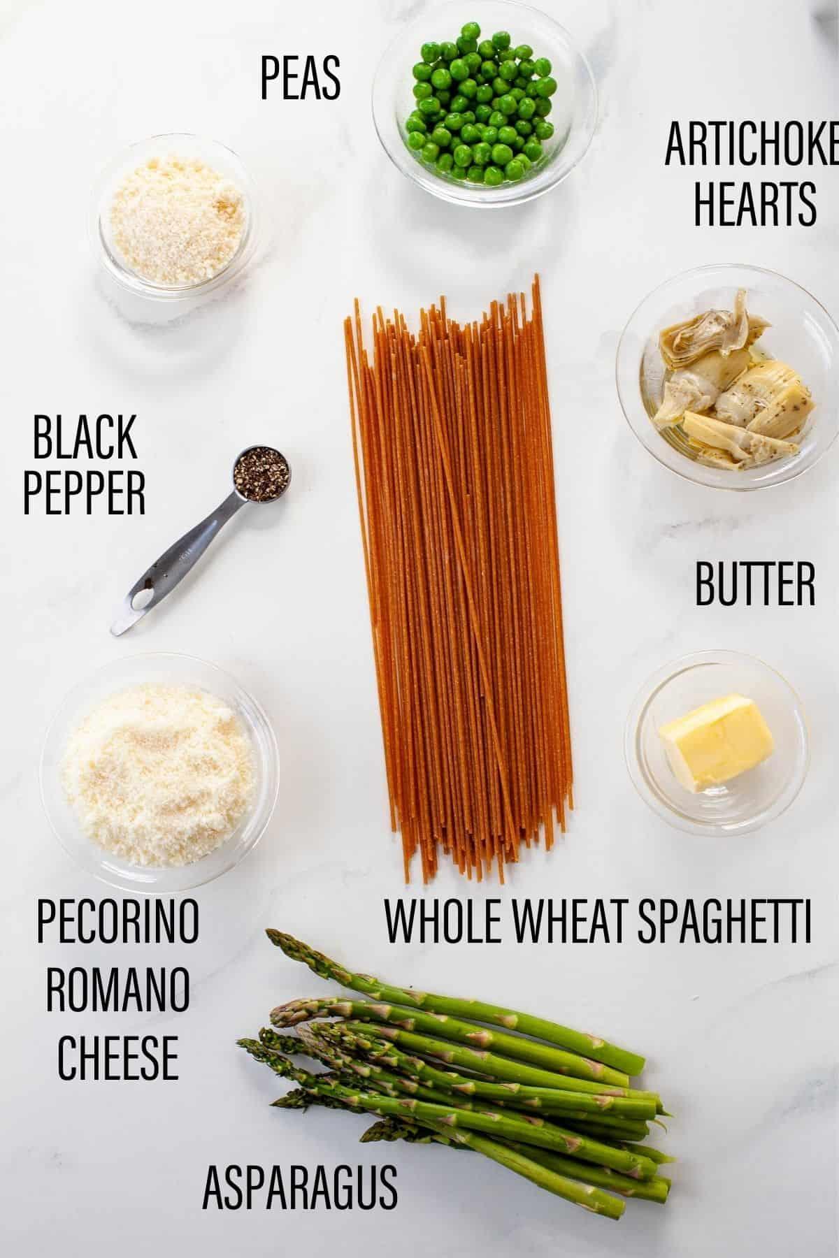 spring vegetable pasta ingredients on white surface whole wheat spaghetti, peas, artichoke, asparagus, pecorino romano cheese