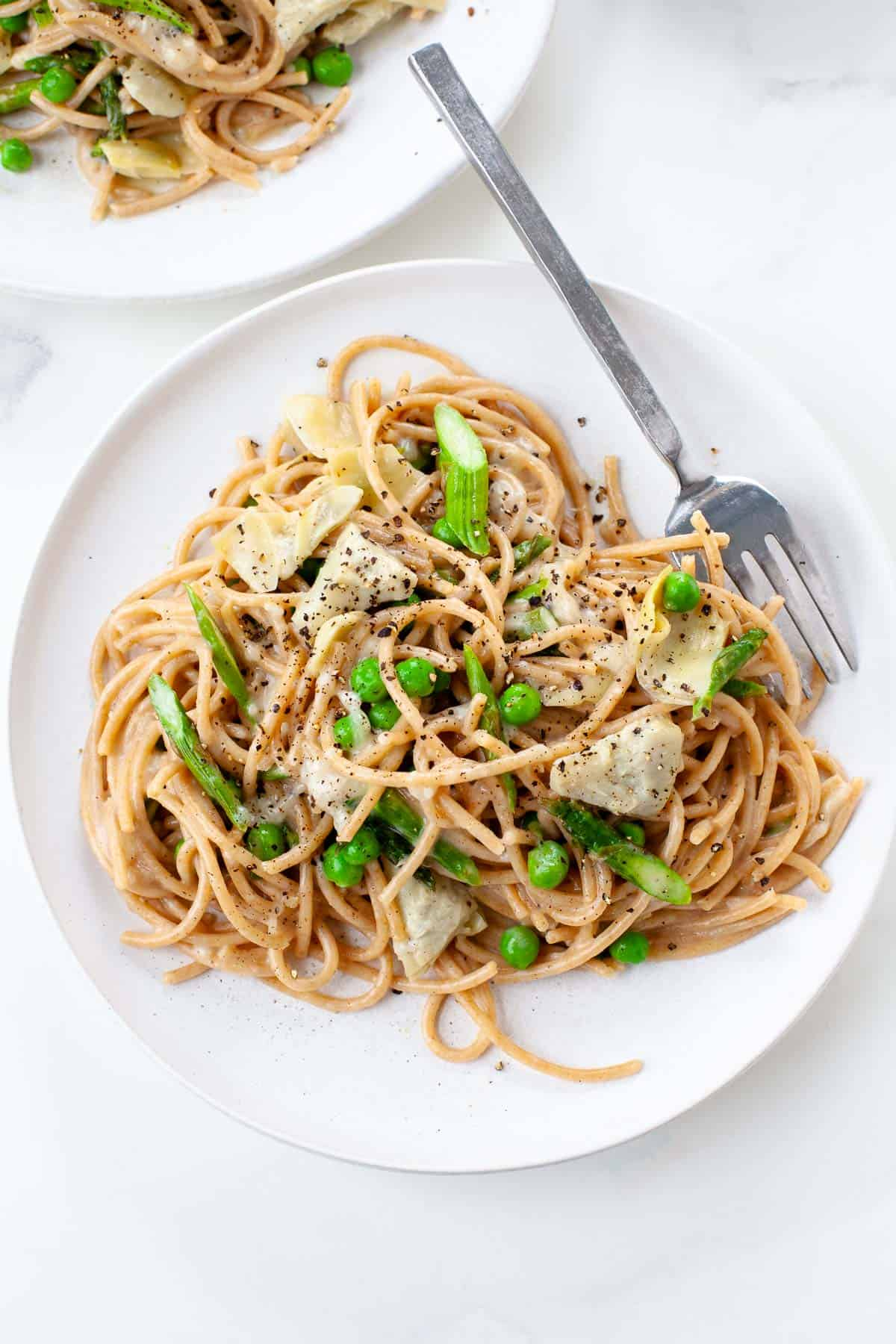 spring vegetable pasta with asparagus, peas, artichokes on white plate with fork white background