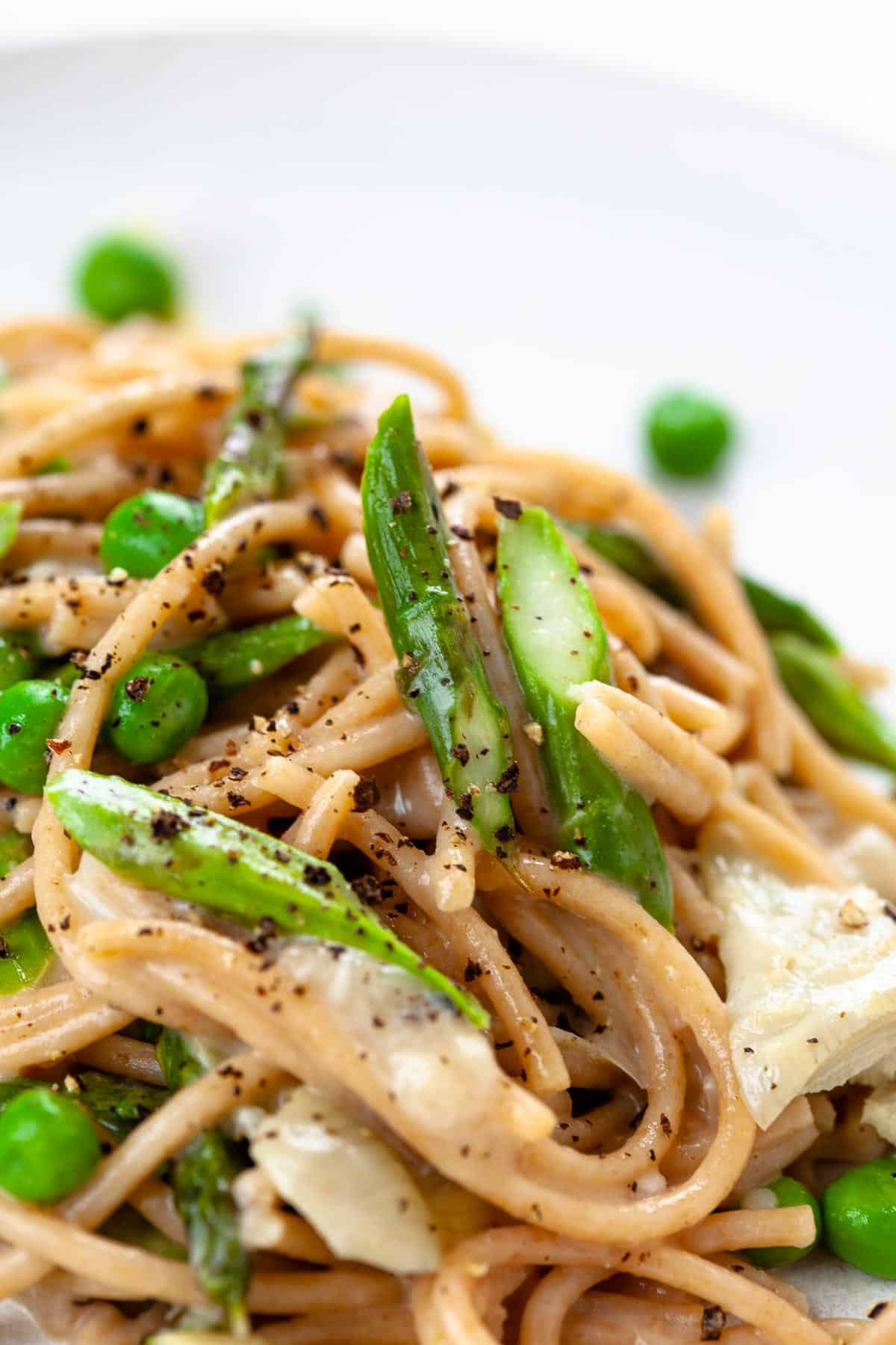 close up spring vegetable pasta with asparagus, peas, artichokes and pepper garnish