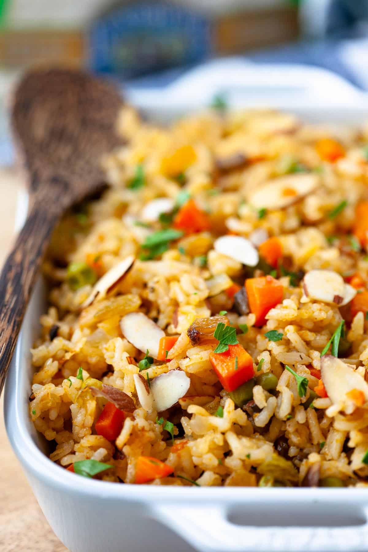 vegetarian rice pilaf casserole dish with wooden spoon long grain white rice, sliced almonds, golden raisins