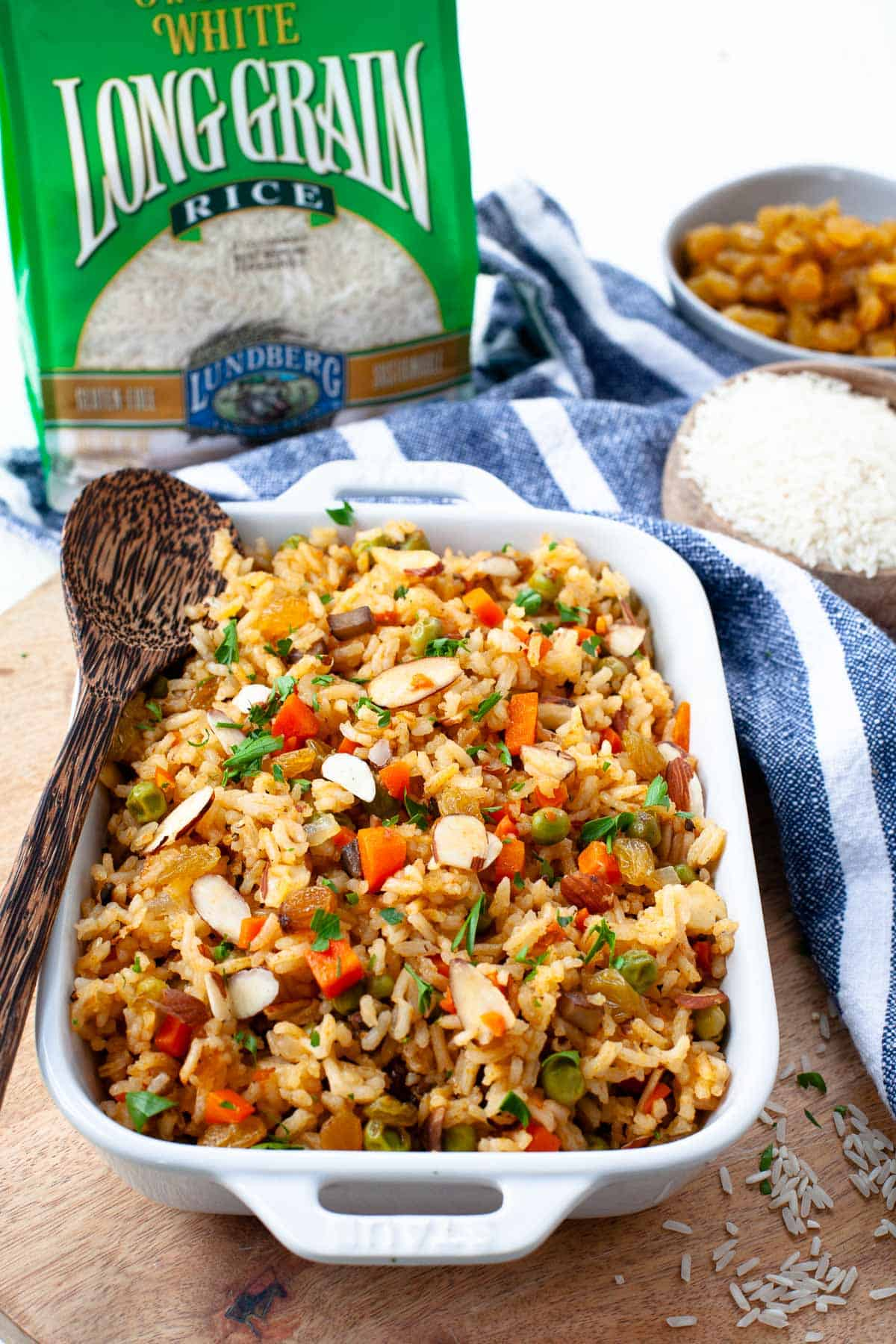 lundberg white long grain rice vegetarian rice pilaf casserole dish wooden spoon, blue towel, rice bowl