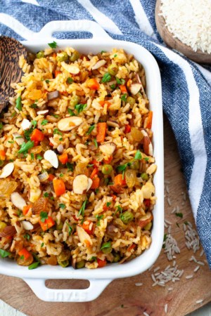 vegetarian rice pilaf in casserole dish with long grain white rice, sliced almonds, golden raisins