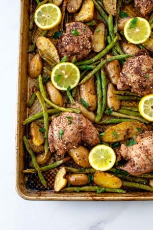 sheet pan chicken potatoes and green beans four marinated chicken thighs, five sliced lemon on pan