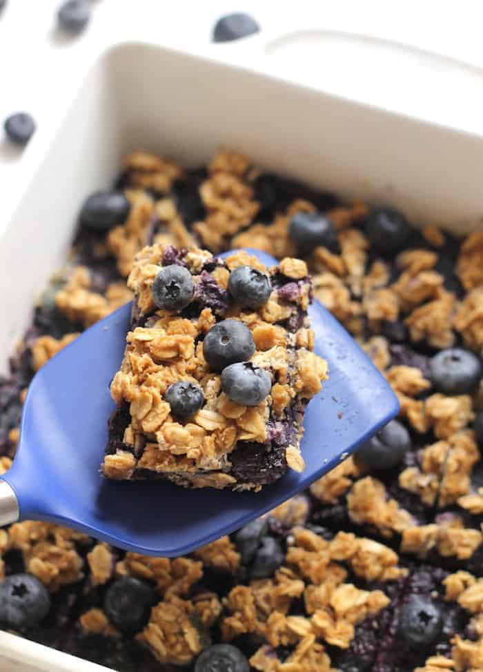 Blueberry oatmeal snack bars, fresh blueberries on top, one slice taken out of square baking pan