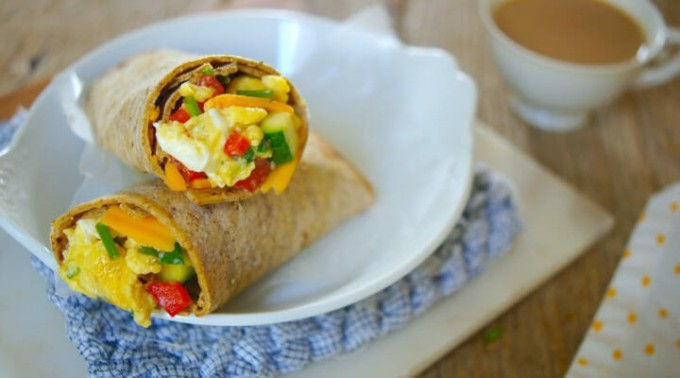 Freezer-friendly breakfast egg wrap on white plate, cup of coffee on the side