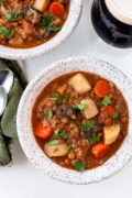 up close vegetarian irish stew with carrots, lentil, parsley garnish in gray bowl guinness beer stout