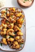 up close crispy crunchy golden brown air fryer cauliflower white background with garnish