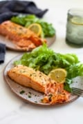 air fryer salmon fresh and frozen salmon fillet flakes two plates with lemon slice and lettuce